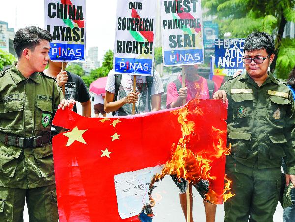 지난달 필리핀 마닐라시내의 중국영사관 근처에서 필리핀 시위대가 중국의 남중국해 점거를 규탄하며 중국 국기를 불태우는 장면이다. AP연합뉴스