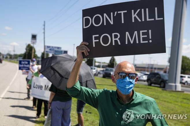 17일(현지시간) 5명을 살해한 사형수 더스틴 호켄의 사형집행에 반대하는 사람들이 그가 수감된 인디애나주 테러호트 연방교도소 인근에서 시위하고 있다. [AP=연합뉴스 자료사진]
