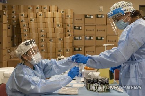 17일(현지시간) 미국 뉴욕에서 텍사스주 휴스턴으로 파견된 의료진이 코로나19 검사 샘플을 다루고 있다. [AFP=연합뉴스]