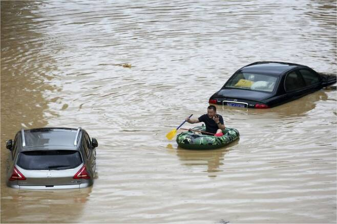 중국에서 한 달 넘게 폭우가 계속되는 가운데 홍수가 발생한 남부 광시좡족자치구 롱슈이 먀오족자치현에서 지난 11일 한 주민이 고무보트를 타고 물에 잠긴 차들 사이를 지나가고 있다. (사진=연합뉴스)