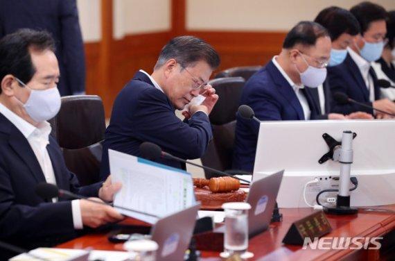 문재인 대통령이 21일 청와대 본관에서 열린 국무회의에 참석해 마스크를 벗고 있다(위 사진은 본 기사와 직접적인 관련이 없음). 뉴시스 제공