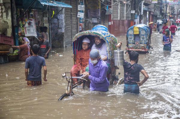 21일 방글라데시 다카의 한 침수된 거리에서 사람들이 인력거에 앉아 있다. 폭우로 수도권 일부 지역이 침수되었다./EPA연합뉴스