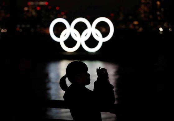 지난 3월 일본 도쿄 오다비아 공원에 설치된 올림픽 오륜기 조형물 앞에서 한 여성이 사진을 찍고 있다. [ 로이터=연합뉴스]