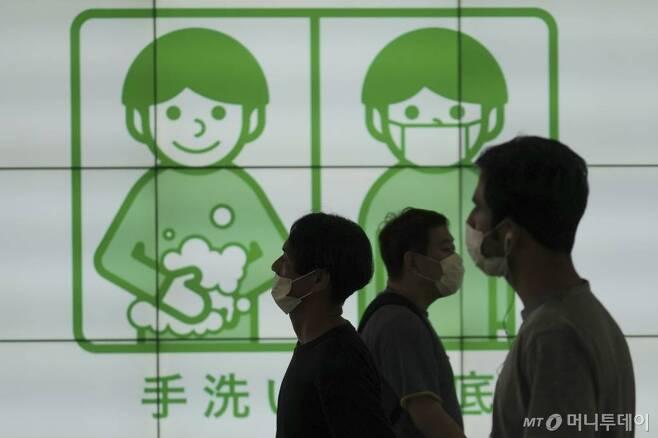 [도쿄=AP/뉴시스]16일 일본 도쿄에서 마스크를 쓴 사람들이 코로나19 예방을 위해 손을 씻자는 현수막 앞을 걷고 있다. 도쿄의 코로나19 신규 확진 사례가 매일 수백 건씩 증가하는 가운데 아베 신조 일본 총리는 외국인 관광객들에게 국경을 닫아 발생한 관광 손실을 상쇄하기 위해 고려했던 국내 여행 장려책 '고 투 캠페인'을 재고해야 할 수도 있다고 밝혔다. 2020.07.16.