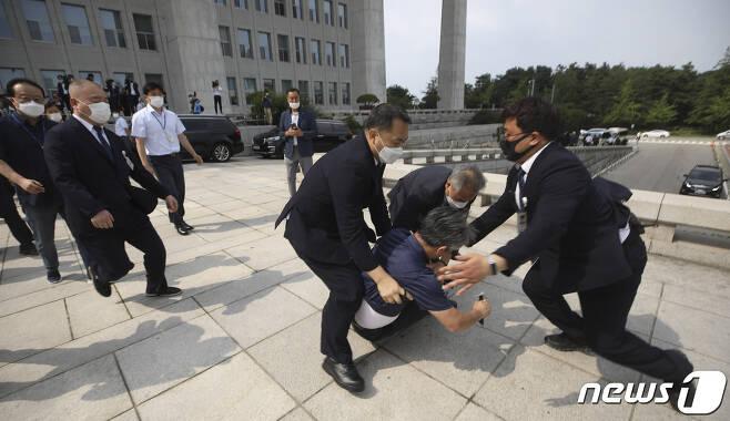 16일 오후 서울 여의도 국회에서 한 남성이 개원 연설을 마친 문재인 대통령을 향해 운동화를 집어던진 후 달려가다가 제지당하고 있다. 2020.7.16/뉴스1 © News1 이동해 기자