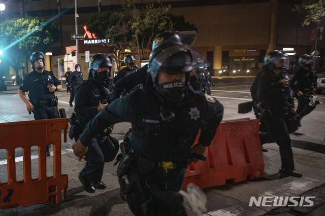 [ 오클랜드( 미 캘리포니아주)= AP/뉴시스] 경찰의 해산 명령에 따르지 않는 시위대를 뒤쫓는 오클랜드 경찰.