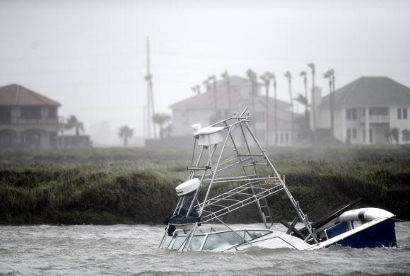 코로나 엎친 데… 시속 145㎞ 허리케인 '해나' 덮쳤다 - 1등급 허리케인 '해나'가 미국 대륙에 상륙한 25일(현지시간) 텍사스주 노스파드리섬에서 선박 한 척이 침몰해 표류하고 있다. 해나는 최대 시속 145㎞의 강풍을 타고 곳곳에 피해를 입혔다. 이날 텍사스주는 코로나19 일일 확진자가 8100명을 넘어섰고 기상재해까지 겹쳐 위기가 더욱 커지고 있다.노스파드리 AP 연합뉴스