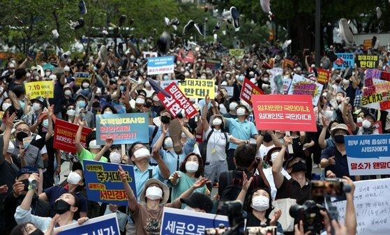 정부의 고강도 부동산 규제에 반발하는 시민들이 지난 25일 저녁 서울 중구 예금보험공사 앞에서 열린 '부동산 규제정책 반대, 조세저항 촛불집회'에서 신발을 던지는 퍼포먼스를 하고 있다. 뉴스1