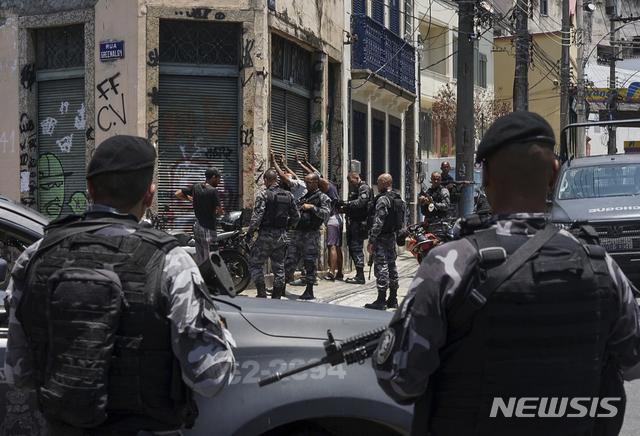 【리우데자네이루=AP/뉴시스】8일(현지시간) 리우데자네이루 인근 산타테레사에서 브라질 특수경찰이 마약 밀매범을 색출하기 위해 남성들을 검문하고 있다.  리우데자네이루 사법 관계자는 산타 테레사 인근 빈민가에서 최소 11명의 마약 밀매 용의자들이 경찰과 총격전 끝에 사살됐다고 밝혔다. 2019.02.09.