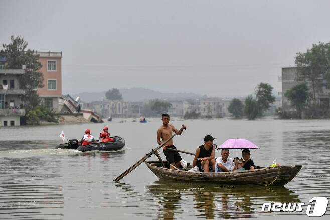 15일 (현지시간) 중국 최대 담수호인 포양호 인근 장시성 상라오의 주민들이 폭우로 물에 잠긴 마을에서 보트를 타고 이동하고 있다. © AFP=뉴스1 © News1 우동명 기자