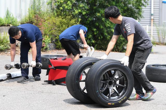 CJ로지스틱스 레이싱팀 미캐닉이 17일 용인 처인구 캠프에서 경기용 차량 타이어와 부품들을 옮기고 있다. 정준희 인턴기자