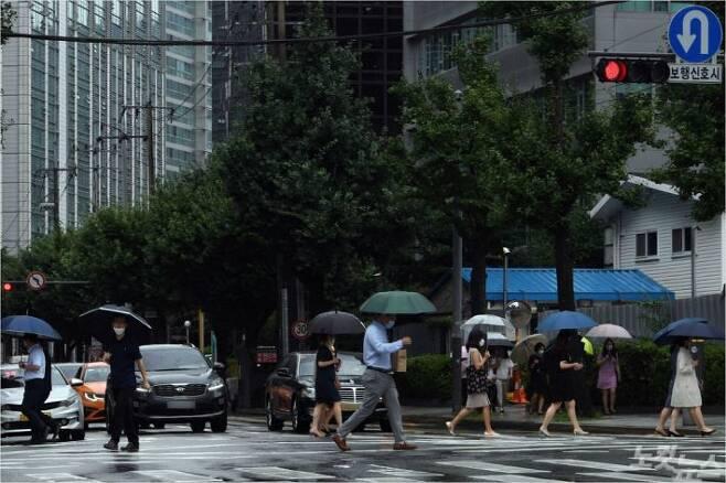 서울·인천·경기 등 수도권에 호우경보가 내려진 3일 오후 정부서울청사 부근 횡단보도에서 시민들이 우산을 쓴 채 길을 건너고 있다. 황진환기자