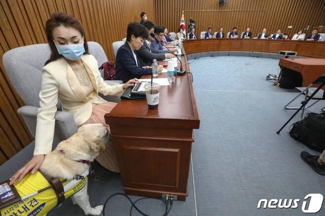 지난 5월26일 국회에서 열린 미래한국당 국회의원·당선인 합동회의에서 김예지 당선인이 안내견 조이를 달래고 있다./사진=뉴스1