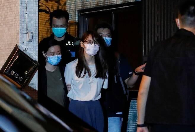 2016년 '우산혁명' 주역인 청년활동가 아그네스 초우(24·가운데)가 10일 밤 홍콩보안법 위반(분리독립 선동) 혐의로 홍콩 경찰에 체포돼 집을 나서고 있다. 초우는 조슈아 웡 등과 함께 2014년 행정장관 직선제를 요구하며 79일 동안 홍콩 도심 점거시위를 이어간 우산혁명을 주도했다. 홍콩/로이터 연합뉴스