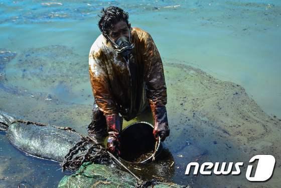 주민과 자원봉사자들이 해안을 뒤덮은 기름띠를 걷어내고 있다. © AFP/사진 = 뉴스1
