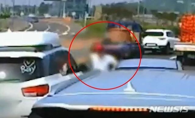 [제주=뉴시스]지난달 4일 제주시 조천읍한 도로 위에서 카니발 차량 운전자 A(35)씨가 주먹을 휘두르고 있다. 경찰은 A씨를 폭행 및 재물손괴 혐의로 입건해 조사 중이다. (사진=유튜브 영상 캡처)