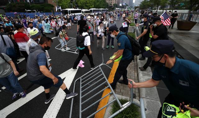 보수단체 집회 참가자들이 15일 오전 서울 종로구 광화문광장에서 8·15 국민대회 집회중 경찰이 세워놓은 바리게이트를 넘어 도로로 나오고 있다.뉴시스