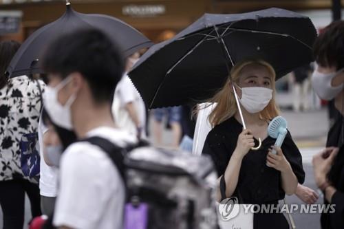 일본 도쿄 번화가인 시부야에서 마스크를 쓰고 걸어가는 행인들. [AP=연합뉴스 자료사진]