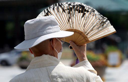 전국 대부분 지역에 폭염 특보가 발효된 19일 오전 서울 광화문 광장 인근에서 마스크를 쓴 시민이 부채로 햇볕을 가리고 있다. 연합뉴스