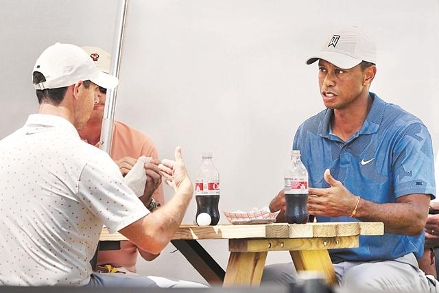 미국프로골프(PGA)투어 플레이오프 1차전 노던 트러스트 3라운드에서 동반 플레이를 치른 '골프 황제' 타이거 우즈(오른쪽)와 로리 매킬로이가 미국 매사추세츠주 노턴의 TPC 보스턴 미디어 센터 옆에 마련된 피크닉 테이블에 앉아 함께 햄버거로 점심 식사를 하고 있다. 신종 코로나바이러스감염증(코로나19)으로 관중 없이 대회가 치러져 이런 한가한 풍경이 가능했다. AP연합뉴스