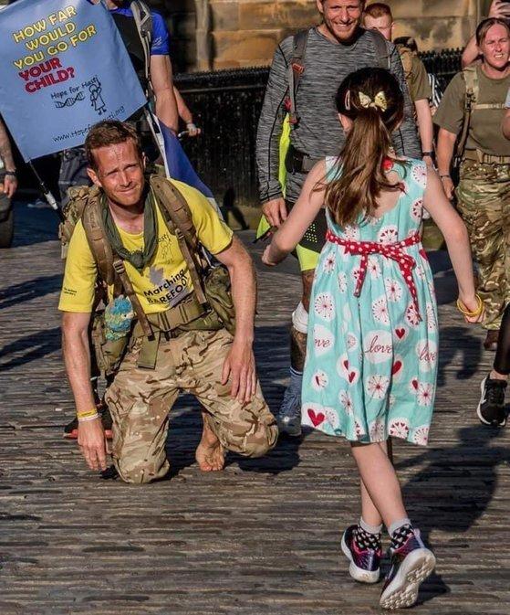 딸을 위해 국토대장정을 마친 브래니건이 마중 나온 딸이 달려오자 안으려 무릎을 꿇고 있다. [트위터 캡처]