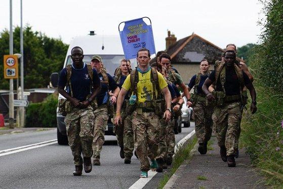 브래니건의 동료들이 그와 함께 걷고 있다. 브래니건은 맨발로 걸어 상처투성이가 된 발에 붕대를 감기도 했다. [트위터 캡처]