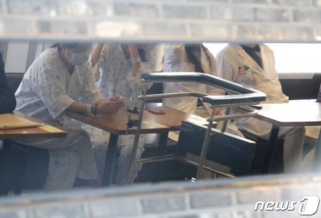 대한의사협회가 사흘간의 2차 전국의사 총파업에 돌입한 26일 서울 종로구 서울대병원에 환자와 의료진이 나란히 앉아 있다./사진=뉴스1