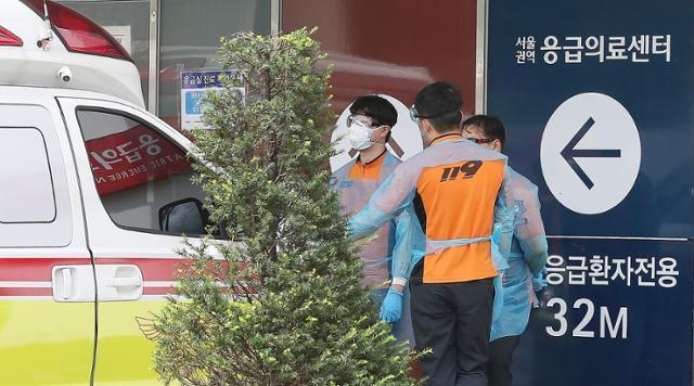 전국의사 2차 총파업(집단휴진) 이틀째인 27일 오후 서울 종로구 서울대병원 응급의료센터 앞에서 119 구조대원들이 응급실 진료 지연으로 대기하고 있다. 뉴스1