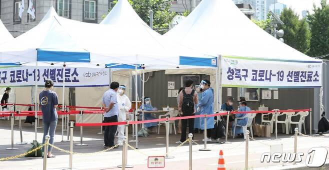 24일 오전 서울 성북구 성북구청 앞에 마련된 코로나19 선별진료소를 찾은 시민들이 검사를 받기 위해 줄지어 서 있다./사진=뉴스1
