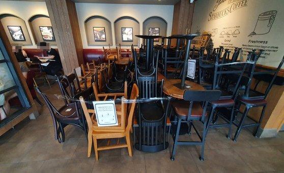 28일 오후 서울 시내의 한 카페에 '사회적 거리두기'를 위해 빼놓은 의자와 테이블이 쌓여있다. 연합뉴스