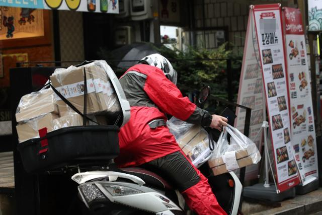 코로나19 재확산으로 매출에 직격탄을 맞은 자영업자들이 배달수수료 인상으로 이중고를 겪고 있는 것으로 나타났다. 사진은 서울 중구의 한 식당가에서 포장음식을 가득 실은 배달원이 배달에 나서는 모습. 연합뉴스