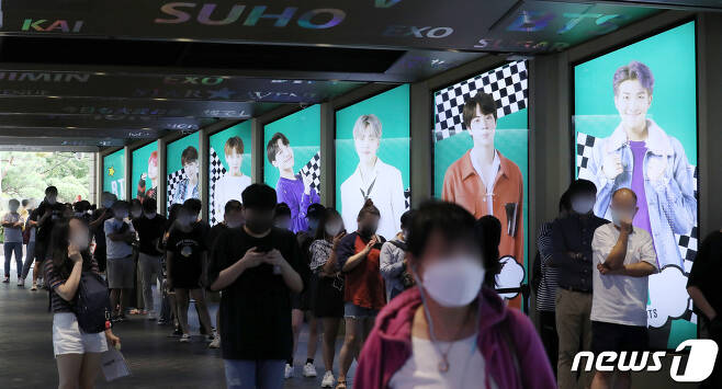 서울 중구 롯데면세점에 BTS의 광고판 앞으로 길게 줄을 서 대기하고 있다.  © News1