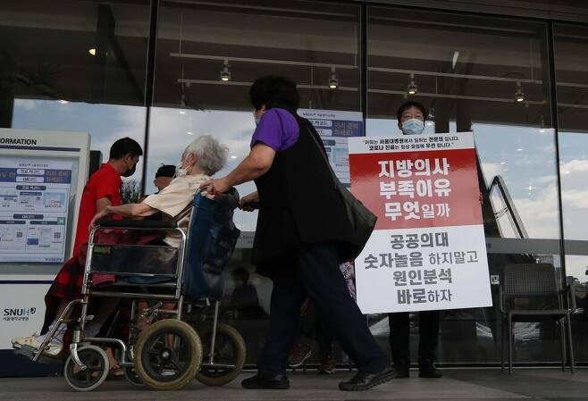 전국 의사 2차 총파업 첫날이 26일 오전 서울 한 대학병원에서 한 의료진이 정부의 공공의료 정책을 규탄하는 대형 팻말을 들고 있다. 백소아 기자