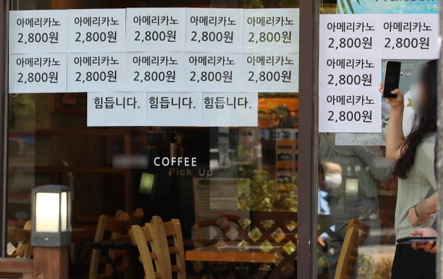 최근 수도권의 코로나19 확산으로 강화된 2단계 사회적 거리두기로 자영업자들의 시름이 깊어지는 가운데 서울의 한 커피 전문점에 '힘듭니다'라는 문구가 적혀 있다. /연합뉴스