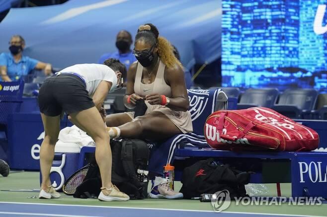 발목 테이핑을 다시하는 윌리엄스(오른쪽) [AP=연합뉴스]
