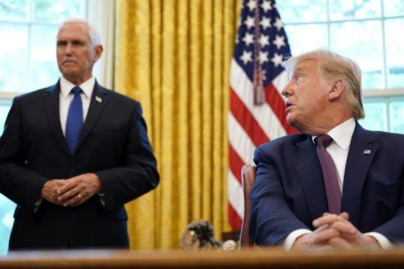 도널드 트럼프 미국 대통령(오른쪽)이 11일(현지시간) 백악관 집무실에서 이스라엘과 바레인 간 국교정상화 합의를 이끌어냈다고 밝히는 기자회견 도중 배석한 마이크 펜스 부통령을 뒤돌아보고 있다. AP뉴시스
