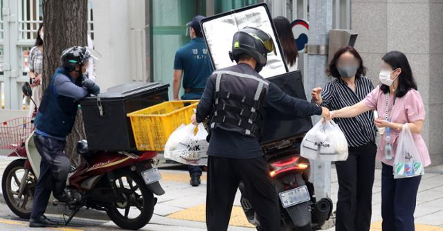 지난 1일 서울 세종대로 정부서울청사에서 공무원들이 오토바이로 배달된 점심 도시락을 받고 있다. 뉴스1