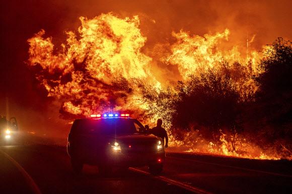 캘리포니아주 고속도로 주변에 번지는 산불 - (오로빌 AP=연합뉴스) 미국 캘리포니아주 오로빌 인근의 162번 주 고속도로 주변에 산불이 번지면서 주행하는 차량들 위로 불길이 치솟고 있다.