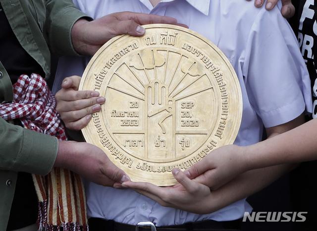 """[방콕(태국)=AP/뉴시스]태국의 민주화 학생 지도자들이 20일 수도 방콕의 수남루앙 광장에서 열린 반정부 시위 중 """"태국은 한 개인의 것이 아니라 국민의 것""""이라고 선언하는 놋쇠 명판을 들어 보이고 있다. 1932년 태국이 절대왕정에서 입헌군주제로 바뀐 것을 기념하기 위한 이 명판은 방콕 왕립광장에 설치돼 있었지만 3년 전 훼손돼 사라졌고 군주제를 찬양하는 내용으로 대체됐었다. 2020.9.20"""