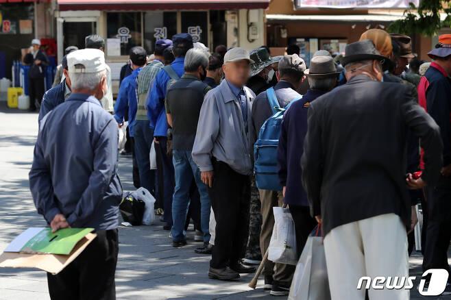 서울 종로구 탑골공원 인근에서 어르신들이 무료급식을 받기 위해 길게 줄 서 있다. 2020.5.8/뉴스1 © News1 이승배 기자