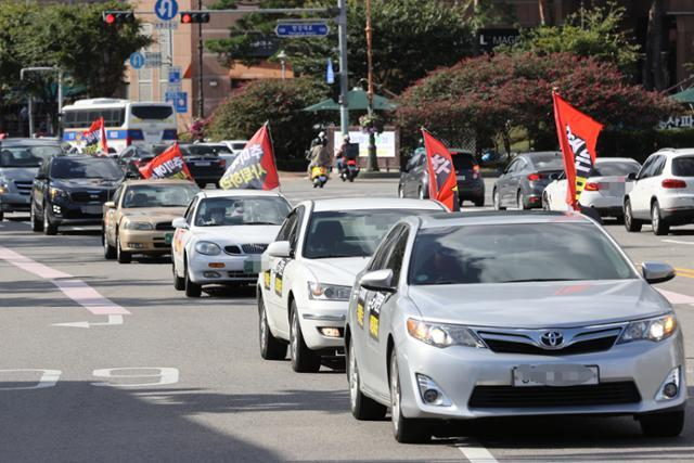 개천절 차량 집회를 예고한 보수단체 '새로운 한국을 위한 국민운동' 회원들이 26일 서울 시내에서 추미애 법무부 장관이 사퇴를 촉구하고 정부의 '반미친중' 정책을 규탄하는 카퍼레이드를 벌이고 있다. 연합뉴스