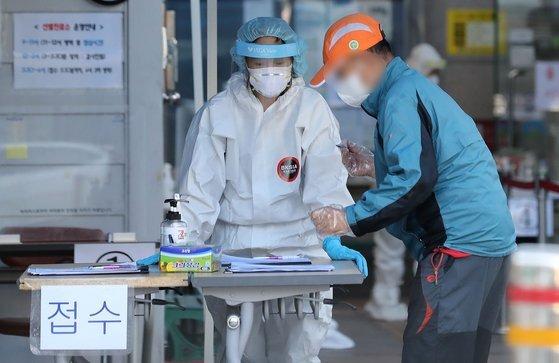 서울 도봉구 한 노인요양시설에서 코로나19 집단감염이 발생한 가운데 27일 도봉구 선별진료소에서 한 시민이 검사를 받기 위해 문진표를 작성하고 있다. 뉴스1