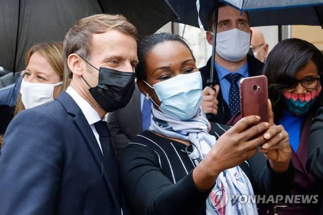 파리 북서쪽 레 뮈로를 찾아 주민과 사진을 찍고 있는 마크롱 대통령 [AFP=연합뉴스]