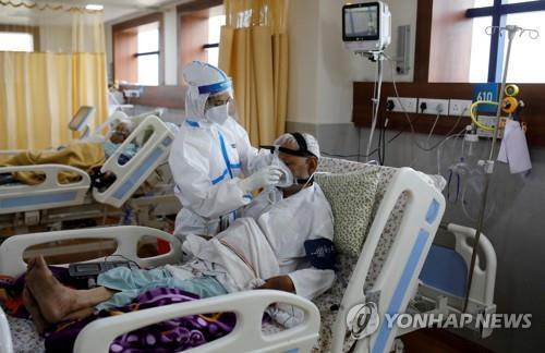 인도 뉴델리의 한 병원에서 코로나19 환자를 돌보는 의료진(왼쪽). [로이터=연합뉴스]
