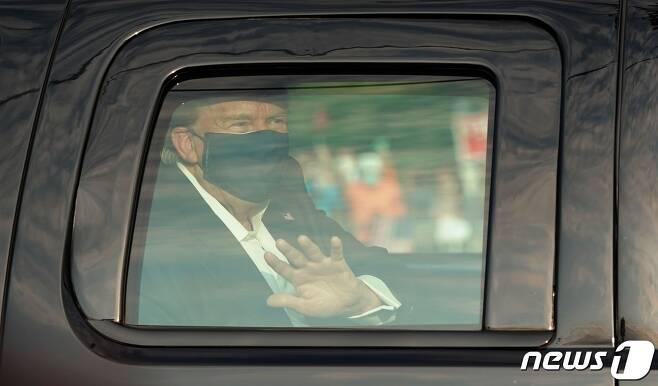 도널드 트럼프 미국 대통령이 4일(현지시간) 코로나19로 입원 중인 메릴랜드주 베세스다에 있는 월터 리드 군 병원 밖으로 차를 타고 나와 지지자들 앞을 지나면서 손을 흔들고 있다. © AFP=뉴스1 © News1 우동명 기자