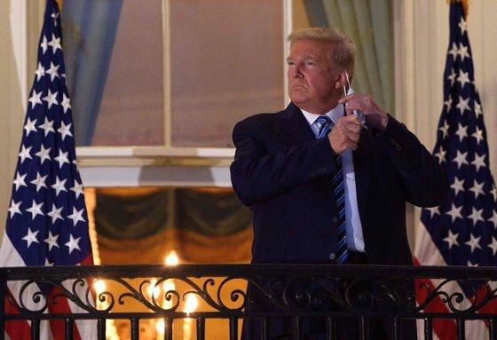 도널드 트럼프 미국 대통령이 5일 월터리드 군병원에서 퇴원해 백악관에 복귀한 뒤 마스크를 벗고 있다. 트럼프는 완치되지 않았는데 퇴원해 바이러스를 전파할 수 있는데도 마스크를 벗었다. [AFP=연합뉴스]