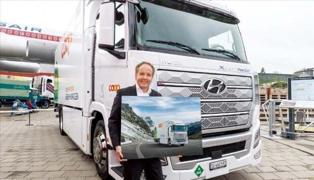 < 수소전기트럭 스위스社에 인도 > 현대자동차는 7일(현지시간) 수소전기트럭 엑시언트 FCEV를 스위스 고객사 7곳에 전달했다. 차량을 인수한 스위스 마트·물류기업 쿠프(Coop) 관계자가 엑시언트 앞에서 환하게 웃고 있다.  현대자동차 제공