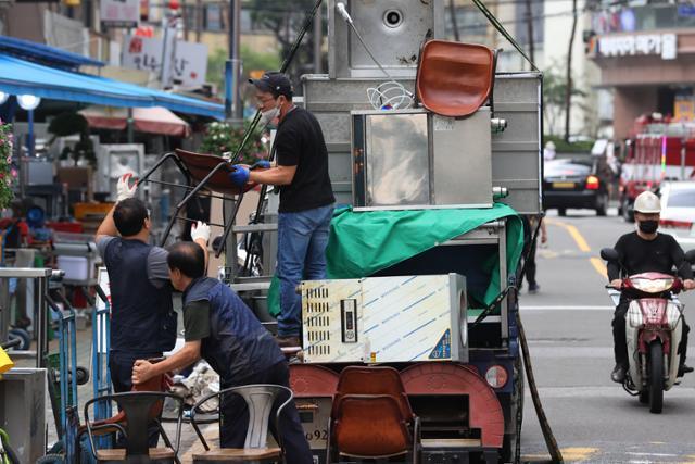 지난달 16일 오후 서울 중구 황학동 주방거리에서 상인들이 폐업식당에서 사들인 중고 식당가구와 주방기구를 트럭에서 내리고 있다. 연합뉴스