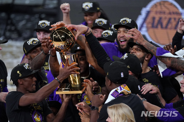 [올랜도=AP/뉴시스]LA 레이커스 선수들이 11일(현지시간) 미 플로리다주 올랜도의 어드벤트헬스 아레나에서 열린 2019~20 미 프로농구(NBA) 챔피언결정전(7전4승제) 6차전에서 마이애미 히트를 물리치고 우승 후 트로피와 함께 자축하고 있다. 레이커스는 마이애미 히트를 106-93으로 꺾어 4승 2패로 우승하며 10년 만에 정상에 복귀했다. 르브론 제임스는 최우수선수(MVP)로 선정됐다. 2020.10.12.