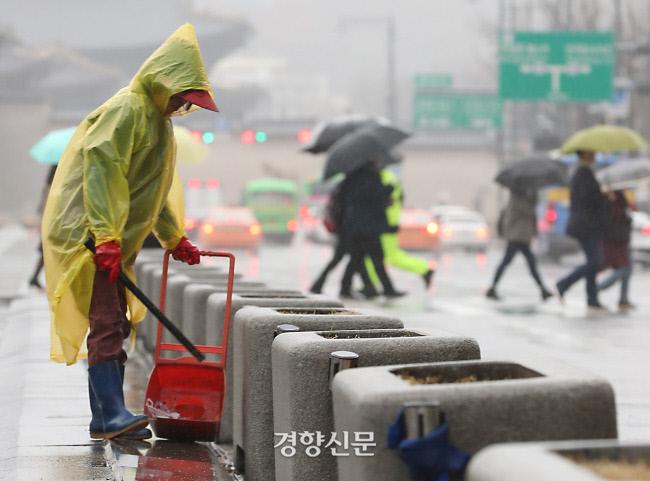 환경미화원이 서울 광화문광장에서 비옷을 입고 청소를 하고 있다. 권도현 기자 lightroad@kyunghyang.com
